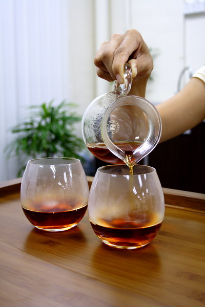 Pour tea from the right end which is supposed to be served for the guest. The one on the left is for the host.