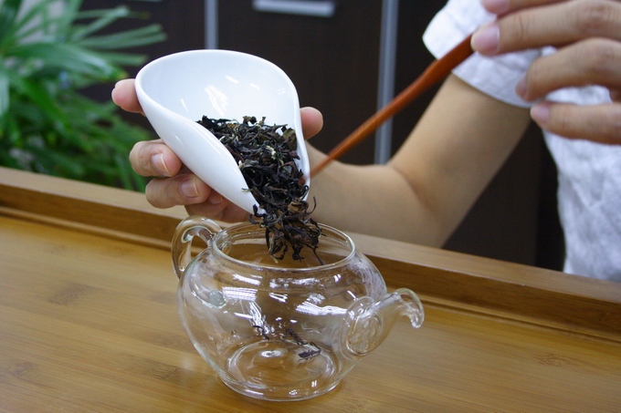 Place the tea leaves into the warmed tea pot. It is important not to touch the tea leaves in order to avoid the contamination of odor.