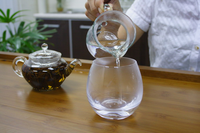 In the mean time, pour off the hot water from the pitcher into the glass to warm it up.