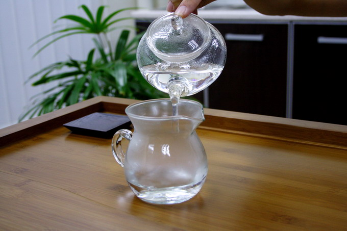 After 20 seconds, remove hot water from the warmed tea pot into the pitcher to warm it up.