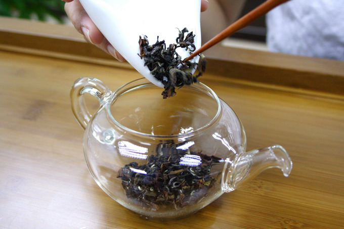 Place the tea leaves into the warmed tea pot. It is important not to touch the tea leaves in order to avoid contamination of odor.
