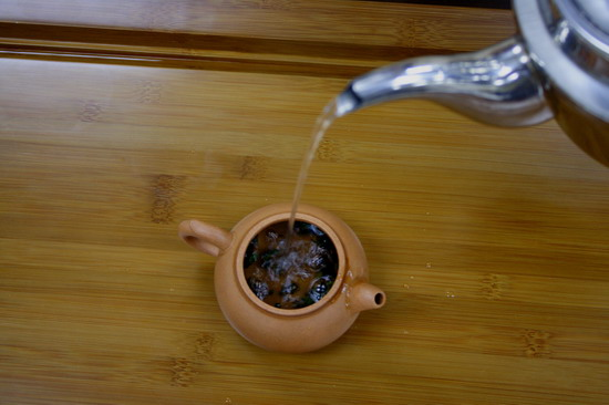Pour boiling water onto tea leaf up to 50% of the volume of tea pot. It is not for washing purpose, but to heat up the tea leaf and open them up.