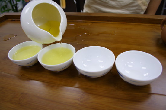 Pour tea from the right end which is supposed to be served for the guest.