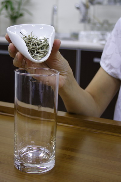 Place tea leaves into the long glass.