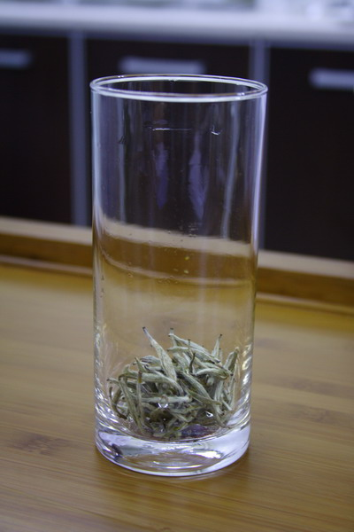 Tea leaves covers the bottom of glass.
